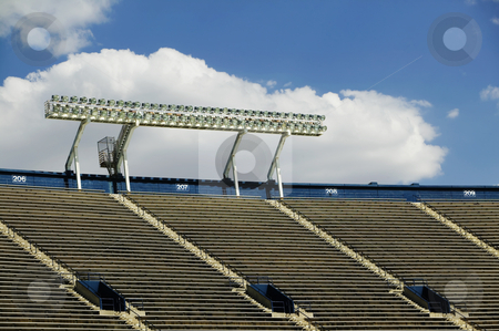 Stadium Lights and a Cloud stock photo, Stadium lights above empty seats with a cloud in the background. by Scott Griessel