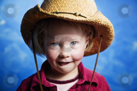 Little girl in front of blue wall with a cowboy hat stock photo, Little girl in front of blue wall wearing a cowboy hat with her tongue out by Scott Griessel