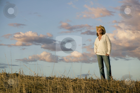 Western Woman Against a Cloudy Sky stock photo, Wide angle shot of a western woman against a cloudy sky at dusk. by Scott Griessel