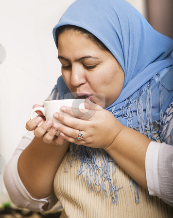 Muslim Woman Drinking Coffee stock photo, Muslim woman wearing a head scarf drinking coffee by Scott Griessel