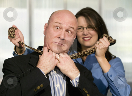 Woman Strangles CoWorker stock photo, Businesswoman strangles a male coworker with his necktie by Scott Griessel