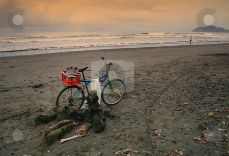 The Fisherman's Bike stock photo, A bike parked on the beach belongs to a fisherman far in the distance. by Scott Griessel