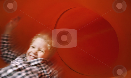 Boy on slide in motion stock photo, Boy slides down an red tube slide with motion blur. by Scott Griessel