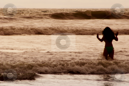 Wading stock photo, A woman in silhouette heads out into the ocean. by Scott Griessel