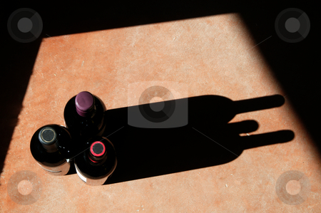 Wine Bottles with Dramatic Shadow stock photo, Wine bottels with heavy side-light and long, dramatic shadow. by Scott Griessel