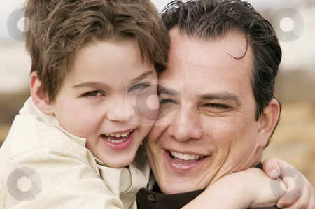 Boy Hugs Man stock photo, Portrait of a young boy hugging a man and laughing by Scott Griessel