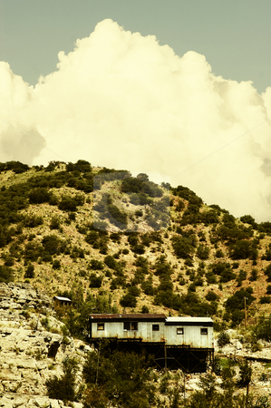 Miner's Shack and Cloud stock photo, Miner's shack on a steep hill with a cloud in the background. by Scott Griessel