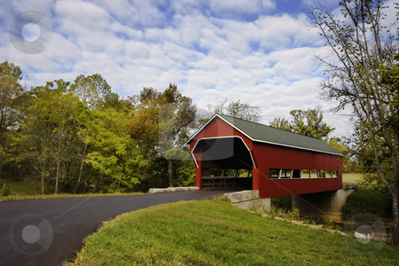 Covered Bridge stock photo, Red covered bridge over a stream during Fall. by Scott Griessel