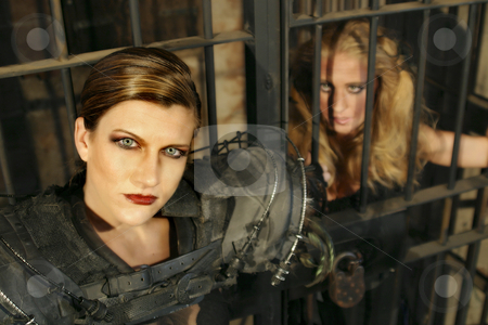 Jailer and Captive 2 stock photo, Close up of a futuristic female guard with her female prisoner looking on. by Scott Griessel