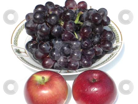 FruitForGoodHealth stock photo, A bowl is filled with fresh black grapes and two red apples are on the side by Rebecca Mosoetsa