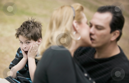 Kissing Adults and Horrified Boy stock photo, Horrified young boy with a kissing couple in the foreground by Scott Griessel