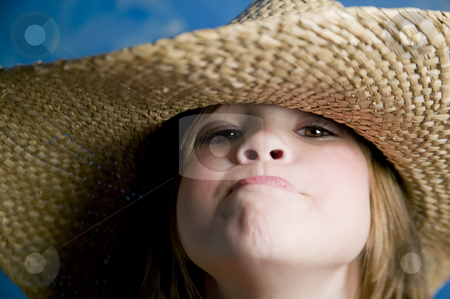Little girl with a straw hat stock photo, Little girl wearing a straw cowboy hat makes a funny face by Scott Griessel
