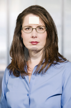 Businesswoman with a blank note on her forehead stock photo, Businesswoman in a blue shirt with a blank sticky note on her forehead by Scott Griessel