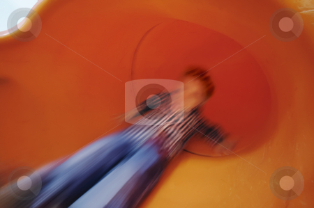 Boy on slide in motion stock photo, Boy slides down an orange tube slide with motion blur. by Scott Griessel