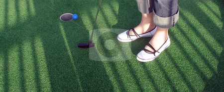 Adventure Golf stock photo, Playing adventure golf, feet, club, ball, hole and shadows. by Lucy Clark