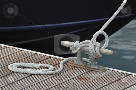 Mooring boat stock photo, Detail of a rope tied up to bitt of a jetty by Massimiliano Leban