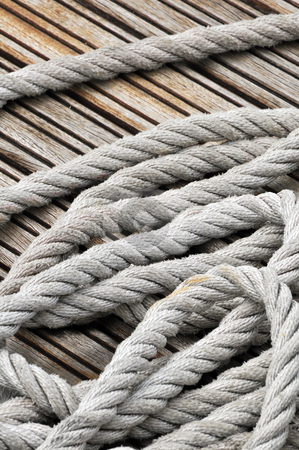 Rope stock photo, Close-up of hank of rope on a wooden jetty by Massimiliano Leban