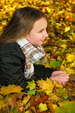Autumn girl stock photo, Portrait of a beautiful teenage girl lying among fallen maple leaves in fall park by Elena Elisseeva