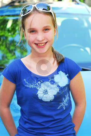 Smiling girl stock photo, Portrait of a smiling young girl sitting on car hood by Elena Elisseeva