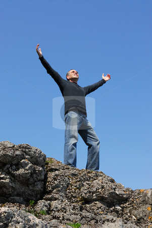Carefree man stock photo, A man standing on a cliff with his arms raised to the blue sky by Elena Elisseeva