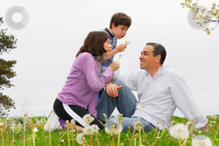 Happy family stock photo, Portrait of a family father and children outside on green grass playing with dandelions by Elena Elisseeva