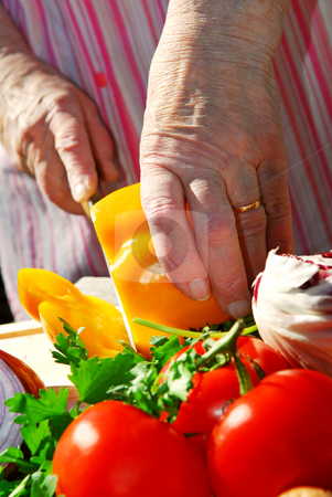Cutting vegetables stock photo, Hands of an elderly woman cutting fresh vegetables by Elena Elisseeva