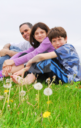 Happy family stock photo, Portrait of a family father and children outside on green grass by Elena Elisseeva