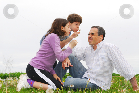 Happy family stock photo, Children playing with their father blowing dandelions by Elena Elisseeva
