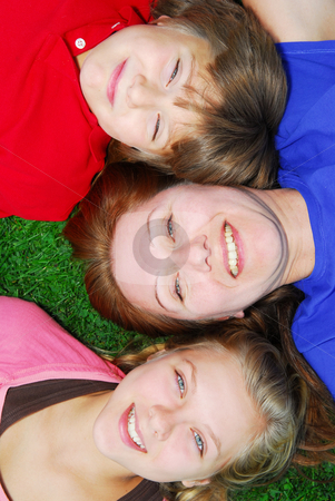 Family lying down on grass stock photo, Portrait of a family - mother and children - lying on grass in a park by Elena Elisseeva