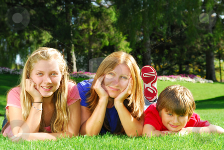 Family relaxing in a park stock photo, Portrait of a family - mother and children - relaxing in summer park by Elena Elisseeva