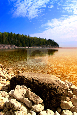 Shore stock photo, Beautiful view on a rocky shore with clear water and golden reflections. Georgian Bay, Canada. by Elena Elisseeva