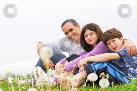 Happy family stock photo, Portrait of a happy family of three on green grass by Elena Elisseeva