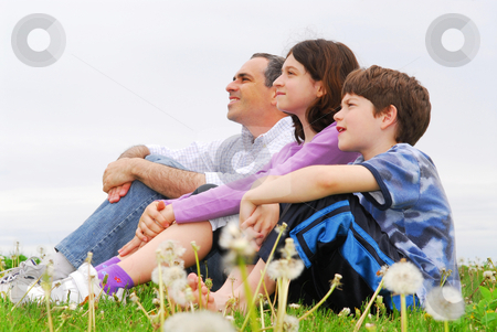 Happy family stock photo, Portrait of a family father and children on green grass by Elena Elisseeva