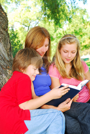Family reading a book stock photo, Portrait of a family - mother and children - reading a book in a park by Elena Elisseeva