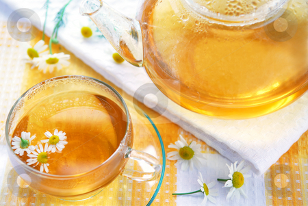 Chamomile tea stock photo, Teacup and teapot with soothing chamomile tea by Elena Elisseeva