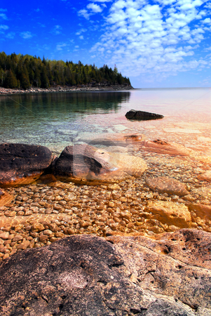 Lake sunset stock photo, Beautiful view on a rocky shore with clear water and golden reflections at sunset. Georgian Bay, Canada. by Elena Elisseeva
