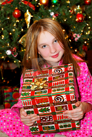Child with Christmas present stock photo, Young girl holding a big Christmas present sitting under a Christmas tree by Elena Elisseeva
