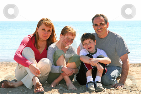 Happy family stock photo, Portrait of a happy family of four sitting on a sandy beach by Elena Elisseeva