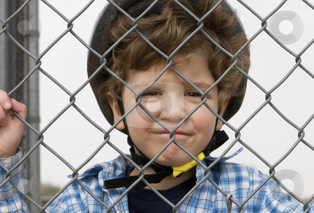 Little boy in a bicycle helmet stock photo, A little boy in a bicycle helmet behind chain link by Scott Griessel