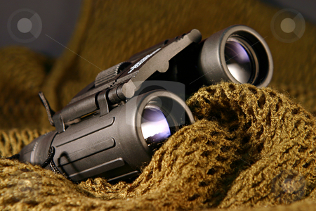 Military spyglass closeup stock photo, A military black spyglass laid on a camouflage mimetic green scarf by Dario Rota