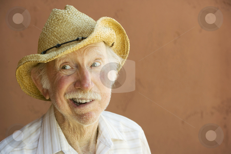 Senior Citizen Man in a Cowboy Hat stock photo, Senior Citizen Man Smiling in a Straw Cowboy Hat With Copy Space by Scott Griessel