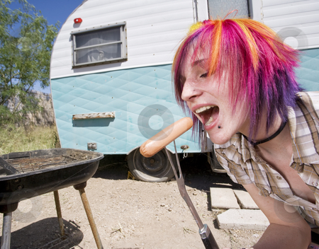 Girl in front of a trailer eating a hotdog stock photo, Girl in front of a trailer with a hotdog and a barbecue by Scott Griessel