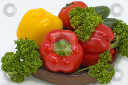 Red and yellow pepper. stock photo, Red and yellow pepper with greens in a basket on a white background. by Yury Ponomarev