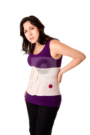Woman with orthopedic body brace stock photo, Woman in pain from back injury wearing an orthopedic body brace corset, isolated. by Paul Hakimata