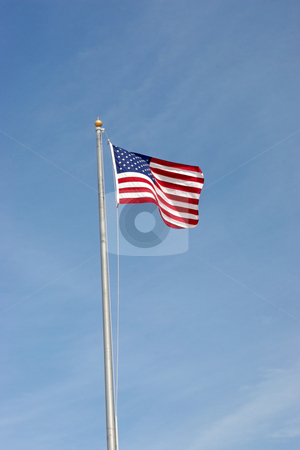 American Flag stock photo, An American Flag flying in the air up a pole by Lucy Clark