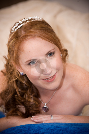 Just married bride laying down with cleavage visible whilst smiling stock photo, red head sexy beautiful bride laying down on her elbows with cleavage visible and leaning on her hands whilst smiling by Ansunette