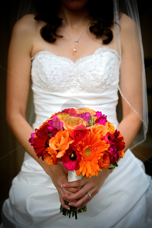 Wedding Flowers and Bride stock photo, A Bride holds her wedding bouquet filled with colorful flowers by Candice Connor