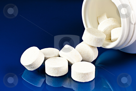 Tablets. stock photo, From an open container of medical pills loose on a blue background mirror.