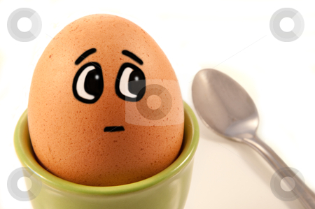 Humorous egg character stock photo, Close up of boiled egg with comic painted face looking worried about the spoon to the side. White background. by Samantha Craddock