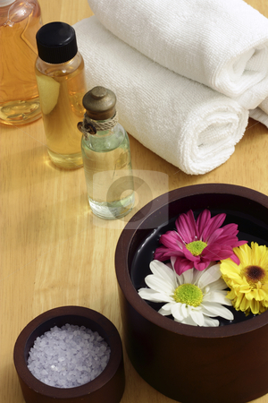 Spa flowers stock photo, A wooden bowl with flowers and some spa items in the background by Adrin Shamsudin